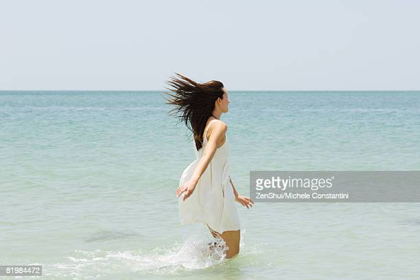young woman at the beach, running knee deep in water, rear view - windswept stock pictures, royalty-free photos & images