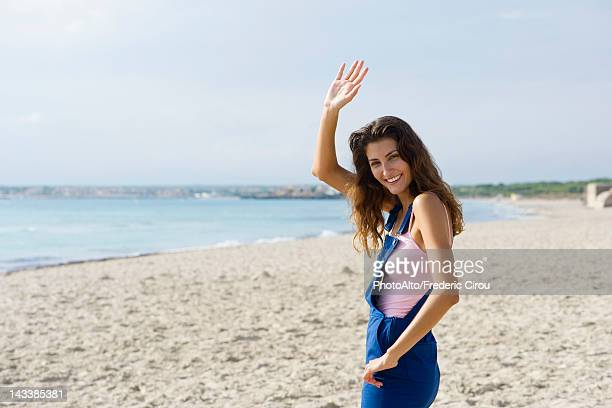 Young woman at the beach, smiling and waving at camera