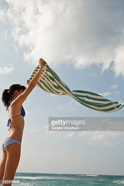 Young woman at the beach with towel.