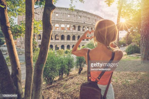 young woman at the colosseum in rome making a heart shape finger frame with hands loving travel in italy - roma stock photos and pictures