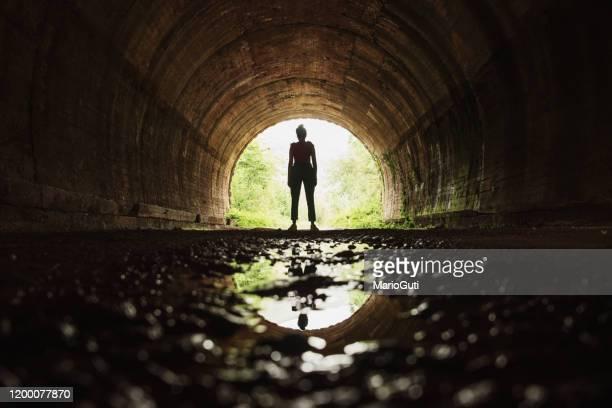 jonge vrouw aan het eind van een tunnel - licht natuurlijk fenomeen stockfoto's en -beelden