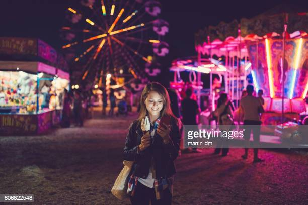 young woman at the funfair text messaging - carnival stock photos and pictures