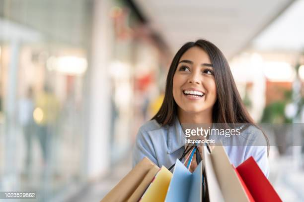 Young woman at the mall looking away imagining positive things while holding shopping bags