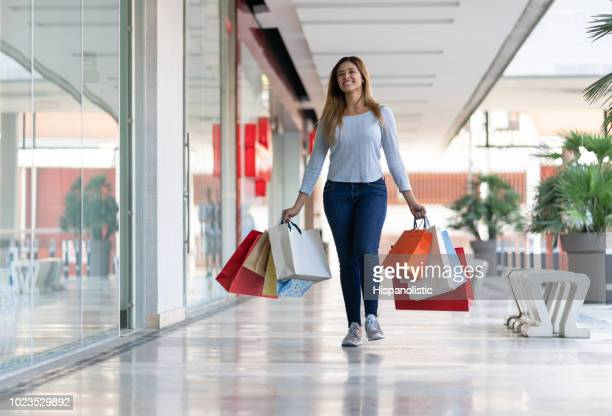 Young woman at the mall looking relaxed and happy shopping while holding bags
