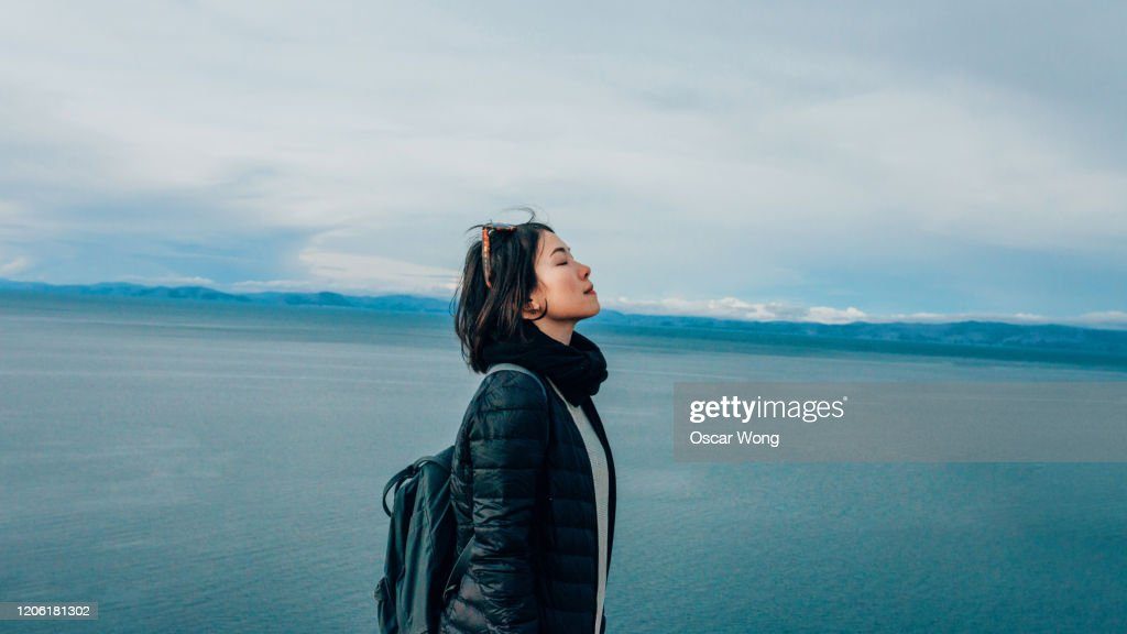 Young Woman At The Mountain Peak, Seaview In The Background : Stock Photo