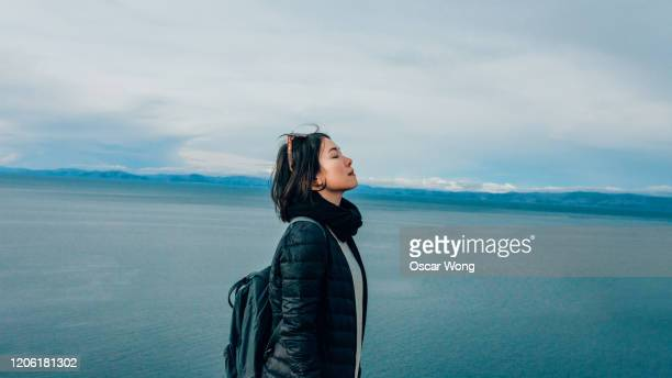 young woman at the mountain peak, seaview in the background - inhaling stock pictures, royalty-free photos & images