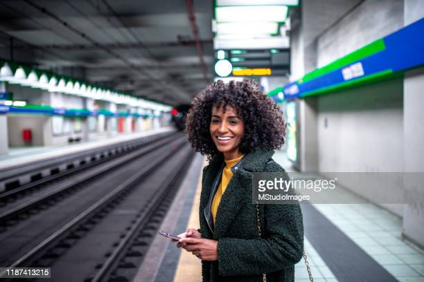 a young woman at the train station holding the phone - underground station stock pictures, royalty-free photos & images