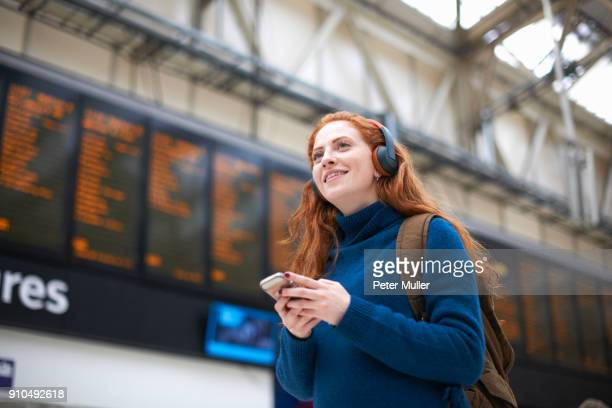 young woman at train station, wearing headphones, holding smartphone - railway station stock pictures, royalty-free photos & images