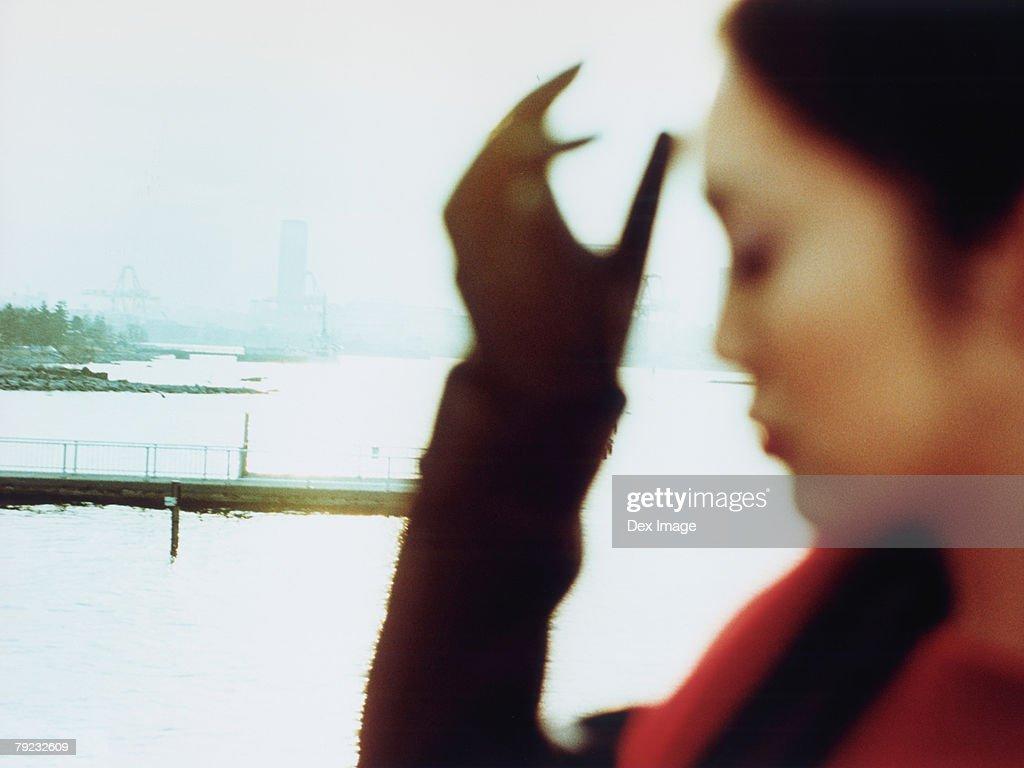 Young woman at waterfront, close up : Stock Photo