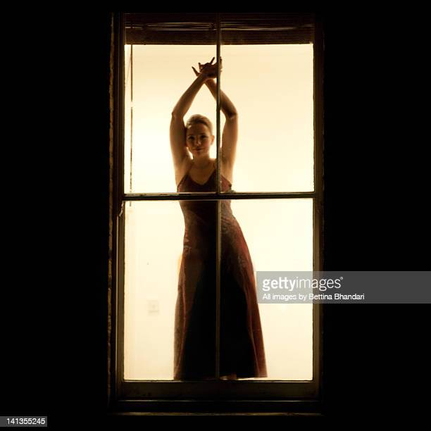 young woman at window - robe longue photos et images de collection