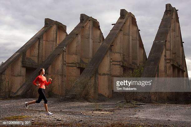 Young woman athlete running by old ruin