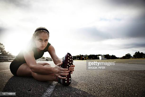 Young woman athlete stretching on track