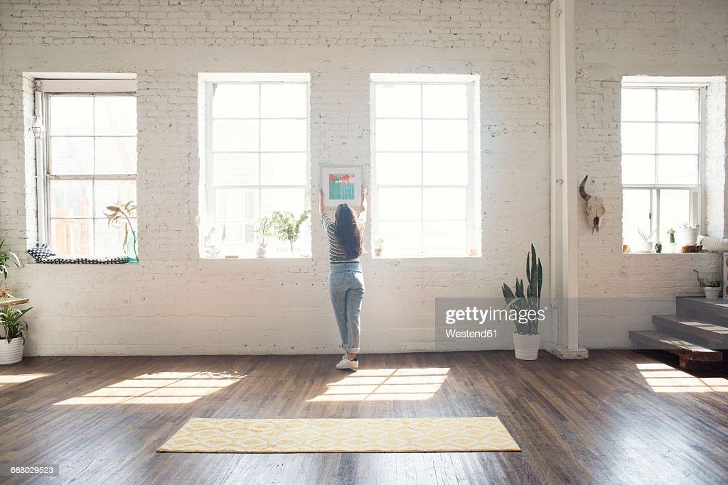 Young woman attaching picture frame to brick wall in a loft : Stock Photo