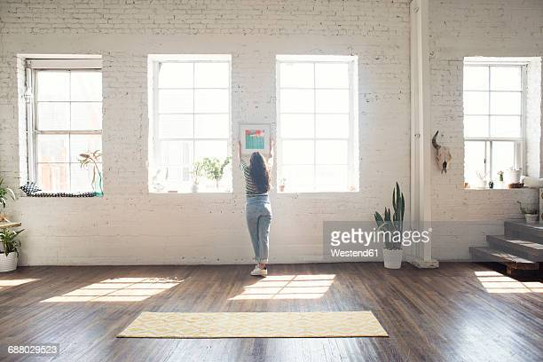 Young woman attaching picture frame to brick wall in a loft