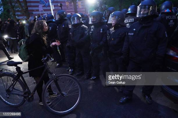 A young woman attempts to get pasrt riot police during scattered leftwing protests in Kreuzberg district on May Day during the novel coronavirus...