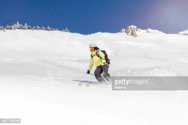 Young woman back country skiing in front of clear blue sky