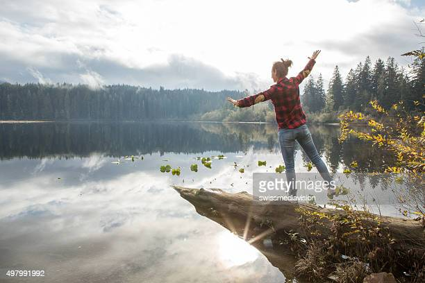 young woman balances on a tree log above the lake - vancouver island stockfoto's en -beelden