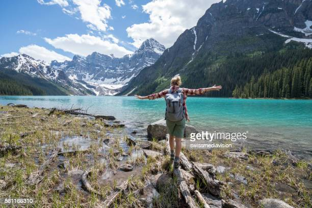 young woman balances on a tree log above the lake - banff national park stock pictures, royalty-free photos & images