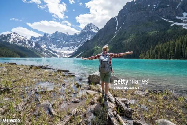 Mujer joven en un árbol saldos registro sobre el lago