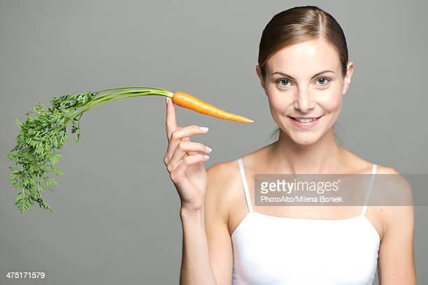 young woman balancing carrot on fingertip - cami fotografías e imágenes de stock