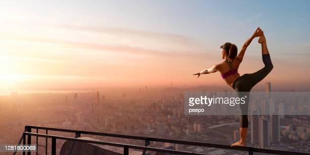 young woman balancing in yoga pose high up over city - active lifestyle stock pictures, royalty-free photos & images