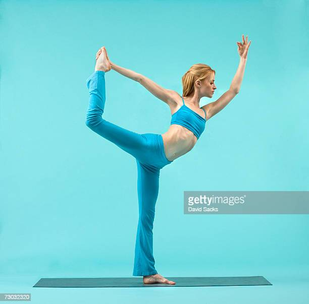 Young woman balancing in yoga pose, side view