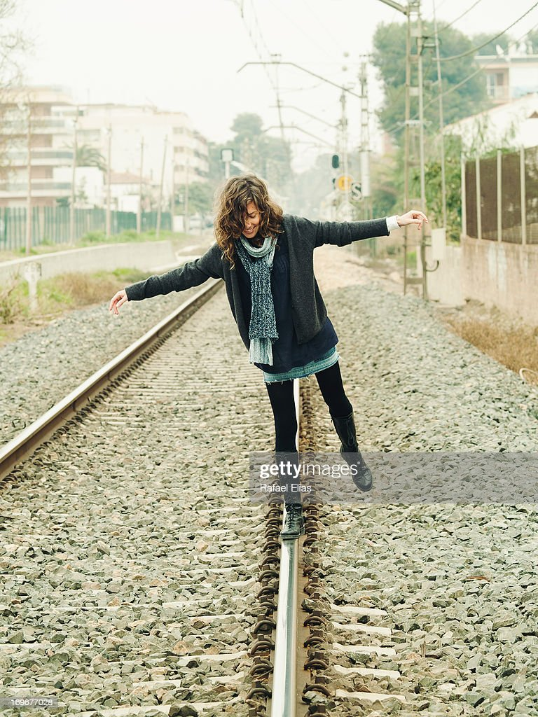 Young woman balancing on a train rail track : Stock Photo