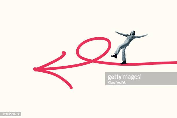 young woman balancing on large pink arrow symbol - part of a series stock pictures, royalty-free photos & images