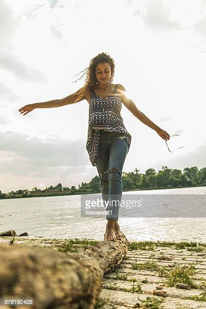 Young woman balancing on log by the riverside