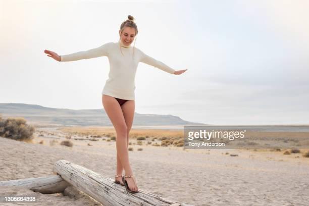 young woman balancing on log on beach - sandale stock-fotos und bilder