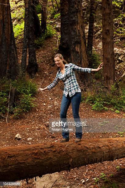 young woman balancing on log