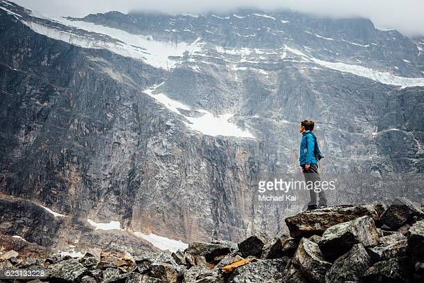 young woman balancing on rocks along angel glacier - michael stock photos and pictures