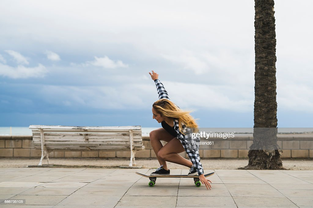 Young woman balancing on skateboard : Stock Photo