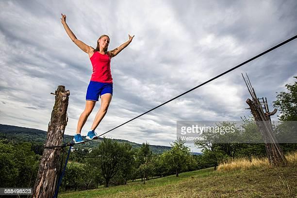 Young woman balancing on slackline