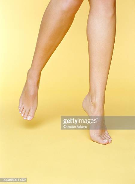young woman balancing on toes of one foot, close-up - white women feet stock pictures, royalty-free photos & images