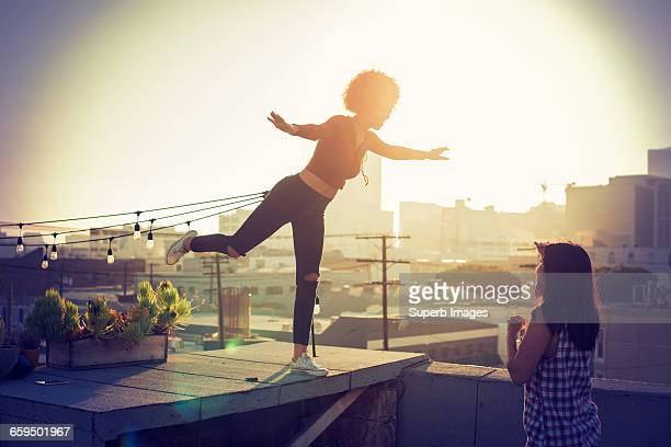 Young woman balancing on urban rooftop