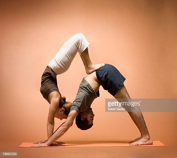 Young woman balancing on young man in yoga pose