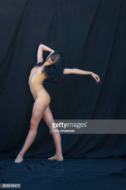 young woman ballet dancer against black background - nude colored shoe stock pictures, royalty-free photos & images