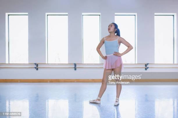 young woman ballet student in rehersal studio warming up for class - rehearsal stock pictures, royalty-free photos & images