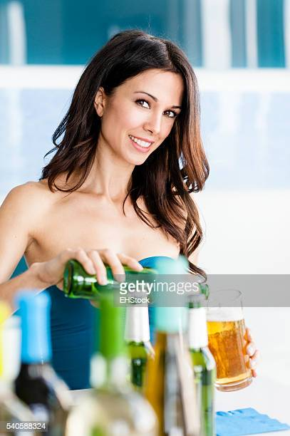 Young Woman Bartender Pouring Beer into Glass