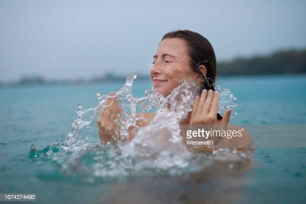 young woman bathing in lake splashing with water - solo adulti foto e immagini stock