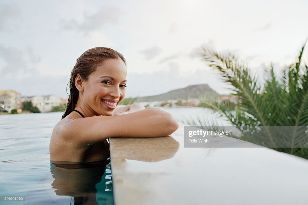 Young woman bathing in swimming pool : Stock Photo
