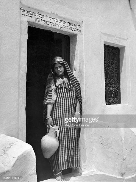 Young Woman Before A House Displaying Hebrew Characters Above The Door In Djerba Around 19501969