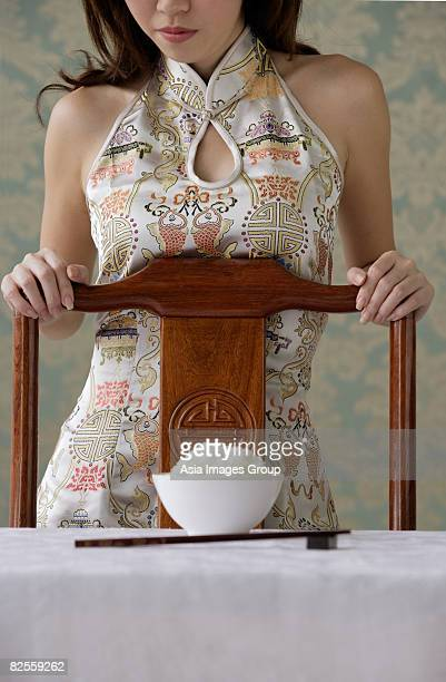 Young woman behind chair with bowl of rice on table