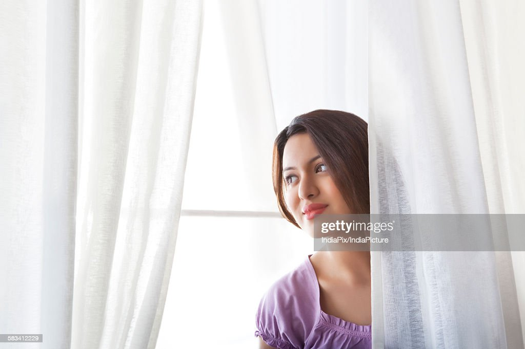 Young woman behind curtains : Stock Photo