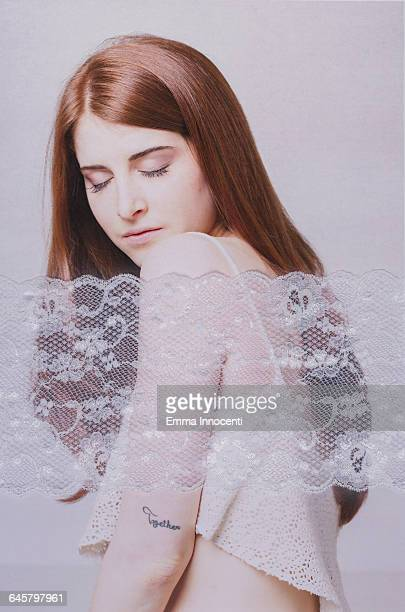 Young woman behind white lace