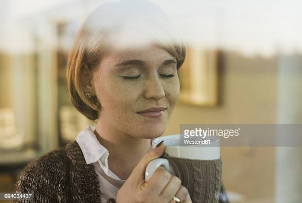Young woman behind windowpane holding a drink in mug