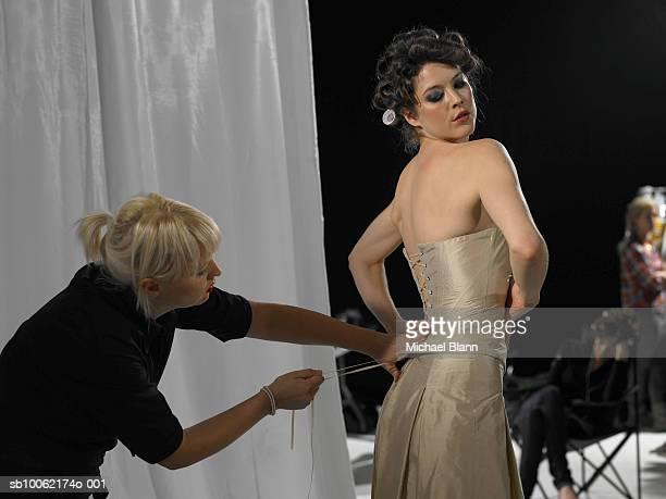 Young woman being dressed back stage, people in the background