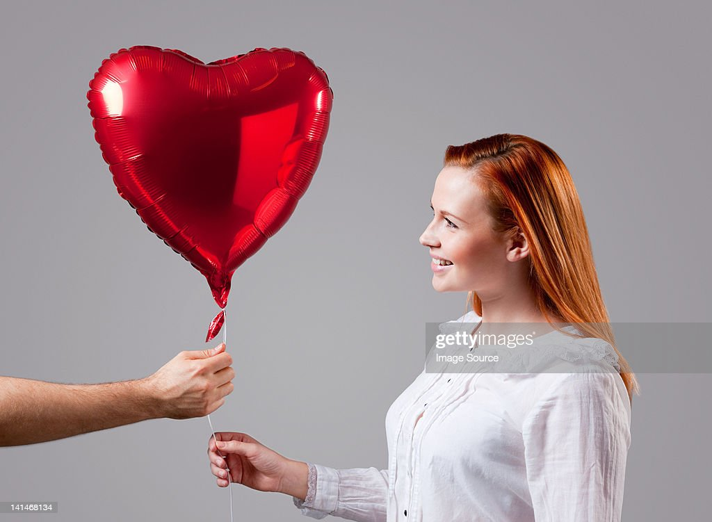 Young woman being given heart shaped balloon : ストックフォト