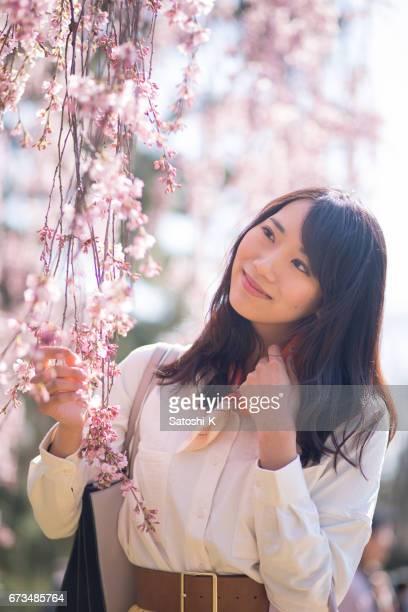 若い女性が桜の花で幸せなこと